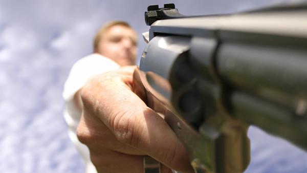 Ein Mann hält eine Waffe in der Hand. Im Gegensatz zur Waffe, ist der Mann nur unscharf zu erkennen.