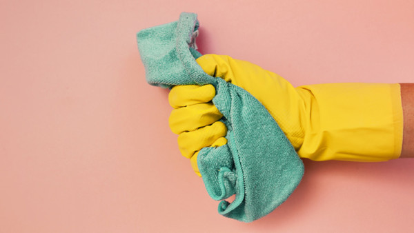 Eine Hand steckt trägt einen gelben Gummihandschuh und hält einen grünen Putzlappen.
