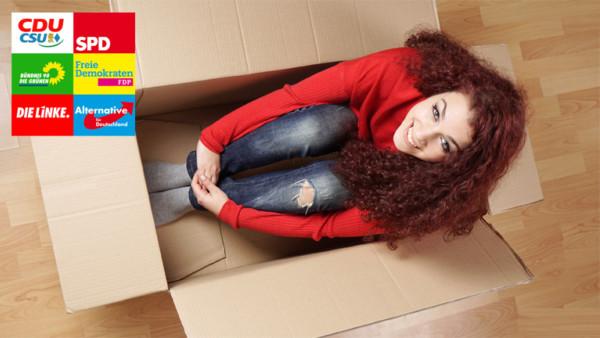 Junge Frau sitzt in einem Umzugsparton