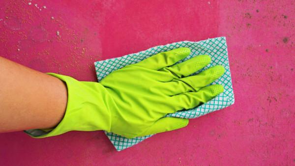 Eine Hand mit Putzhandschuh und Putzlappen.