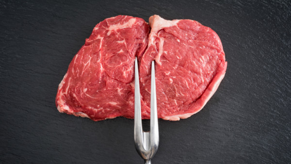 Ein rohes Steak auf einer Gabel.