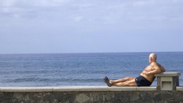 Ein älterer Mann schaut aufs Meer