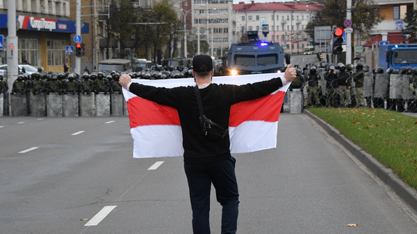 25.10.2020, Belarus, Minsk: A man holds a white-red-white Belarus flags as he attends an opposition rally to reject the presidential election results in Minsk, Belarus.