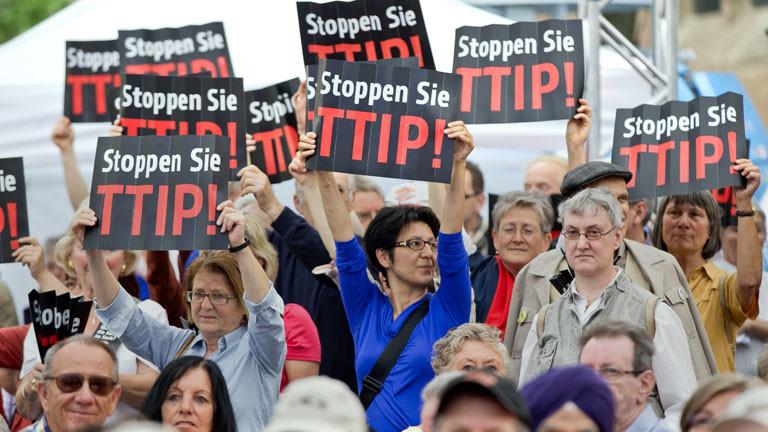 """Zuhörer einer Europawahlkampfveranstaltung der SPD protestieren am 19.05.2014 in Nürnberg (Bayern) mit einem Plakat mit der Aufschrift """"Stoppen Sie TTIP"""" gegen das geplante EU-US-Freihandelsabkommen"""