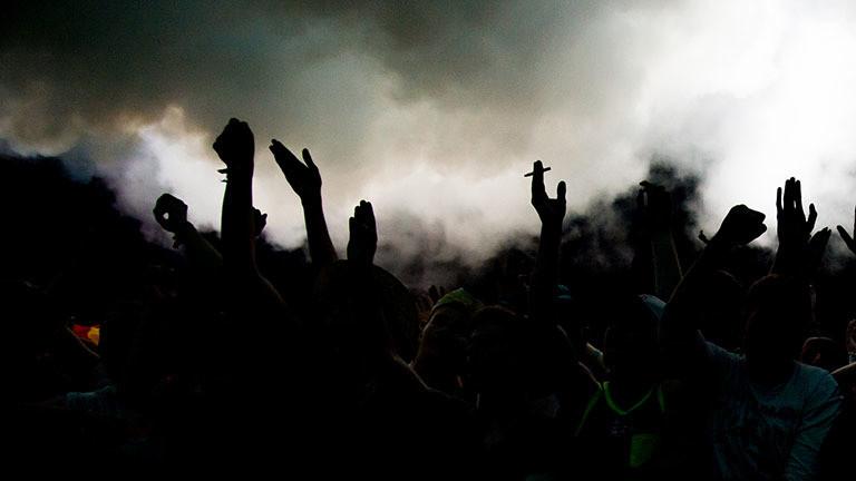 Eine Party draußen: Menschen tanzen und ragen die Hände in die Luft. Es ist dunkel und die Menschen nur schemenhaft erkennbar.