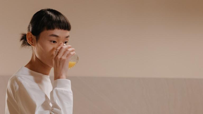 Ein Schluck Saft aus dem Glas: trinkende Frau