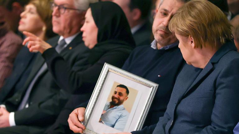 Bundeskanzlerin Angela Merkel (CDU, r) und Angehörige der Opfer nehmen an der Gedenkfeier für die Opfer des Anschlags von Hanau teil.