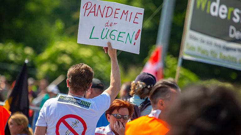 """In Stuttgart demonstrieren Menschen gegen die Corona-Beschränkungen; ein Mann hält ein Schild hoch mit dem Slogan """"Pandemie der Lügen!"""" (16.05.2020)"""