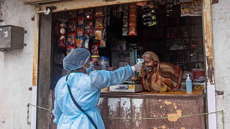 In der indischen Stadt Pune wird einer Ladenbesitzerin über den Tresen hinweg die Körpertemperatur von einer Frau in Schutzanzug gemessen. Sie zielt dafür mit einem Gerät auf die Stirn der Frau. (06.07.2020)
