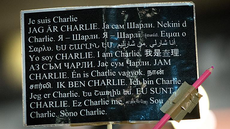 """Ein Teilnehmer hält am 12.01.2015 in Hamburg ein Schild mit der Aufschrift """"Je suis Charlie (Ich bin Charlie) in verschiedenen Sprachen bei einer Kundgebung für Freiheit und Demokratie sowie gegen Terror, Rassismus und Ausgrenzung."""