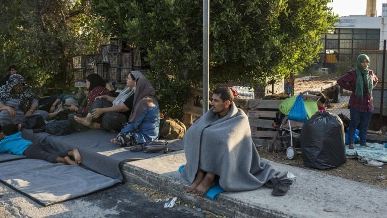 Gelüchtete Menschen sitzen auf der Straße von Lesbos.