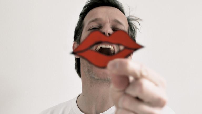 Ein Mann lacht und hält einen roten Papp-Mund vor sein Gesicht.