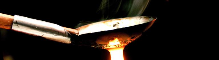Ein Silberlöffel wird über eine Kerzenflamme gehalten.