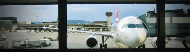 Blick auf das Rollfeld an einem Flughafen. Ein Flugzeug steht direkt vor dem Fenster.