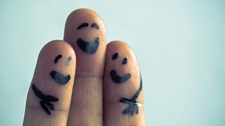 Ring-, Mittel- und Zeigefinger sind nach oben gestreckt. Auf die Fingerkuppen sind lachende Gesichter gezeichnet und auf den beiden Fingern außen jeweils eine Hand.