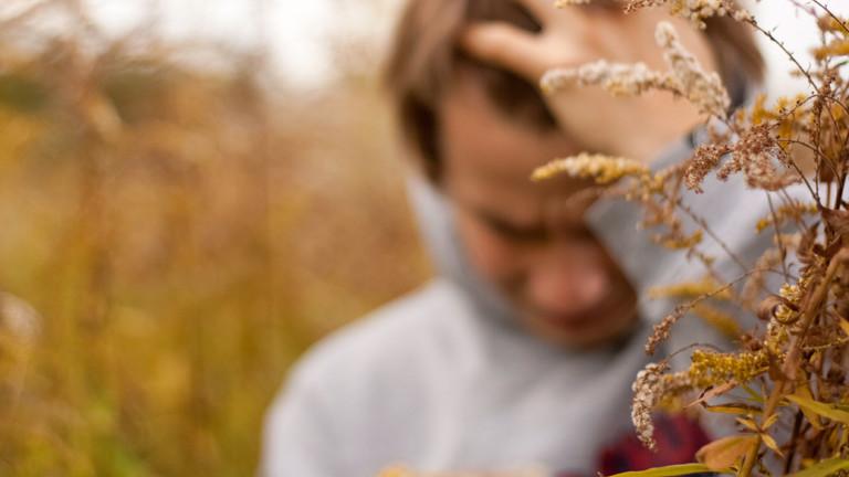Ein Mann fasst mit der Hand an die Stirn und steht im Kornfeld.