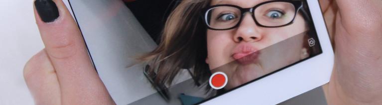 Eine Frau macht ein Selfie im Tablet mit einem Knutschmund.