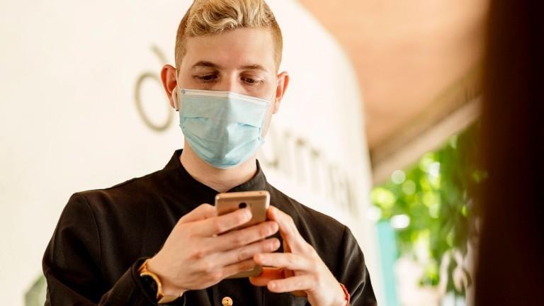 Ein Mann mit einem Mund-Nasen-Schutz schaut auf sein Smartphone