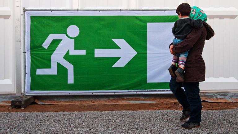 Eine Frau mit einem Kind auf dem Arm vor einem Notausgang-Hinweis