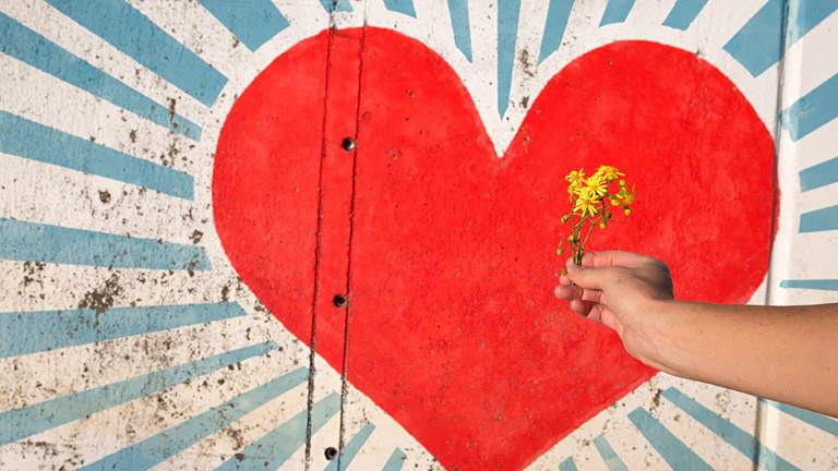 Auf eine Wand ist ein rotes Herz gemalt. Davor hält eine Hand gelbe Blumen.