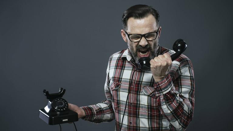 Mann brüllt ins Telefon.