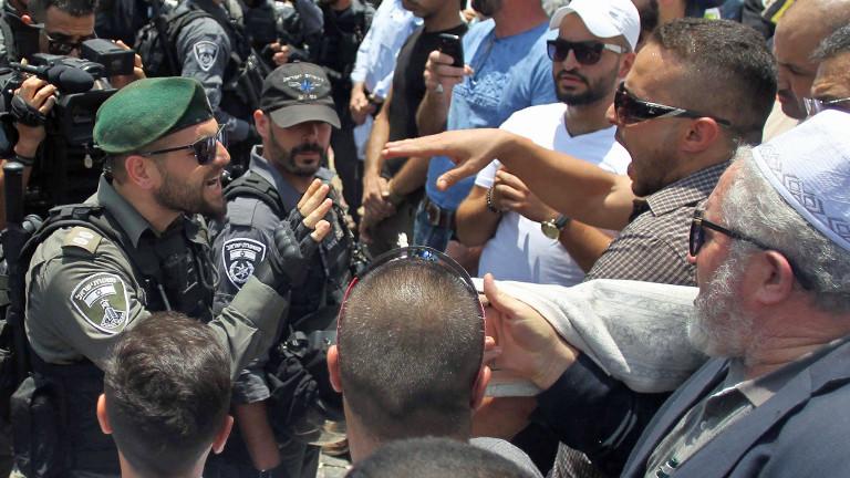 Ein Polizist und Demonstranten geraten in Jerusalem aneinander.