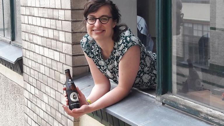Lisa Wiedemuth schaut aus einem Fenster und hat ein Bier in der Hand. Das Label zeigt ein weibliches Konterfei.