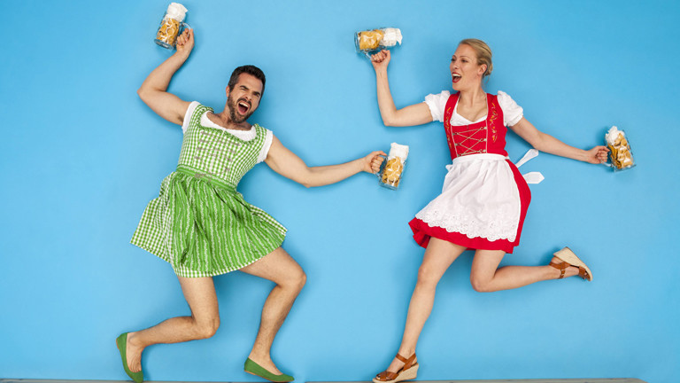 Mann und Frau in Dirndln tanzen mit Bierkrügen in den Händen