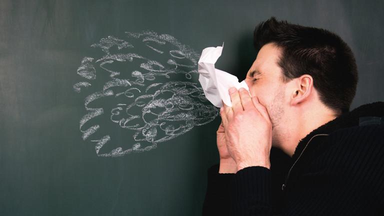Mann niest in Papiertaschentuch