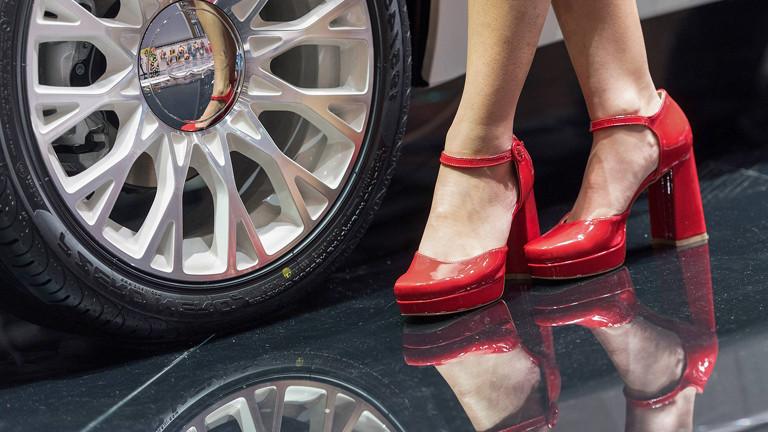 Frauenfüße in roten Heels vor Auto-Felge
