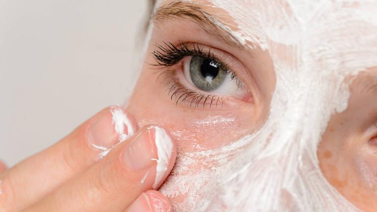 Eine Frau cremt sich das Gesicht ein.