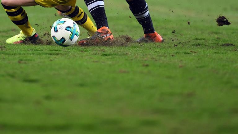 Zwei Bundesligisten bei einem Spiel auf einem Stadionrasen.