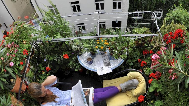 Eine Frau sitzt auf ihrem Balkon und liest Zeitung. Der Balkon ist voller Blumen.