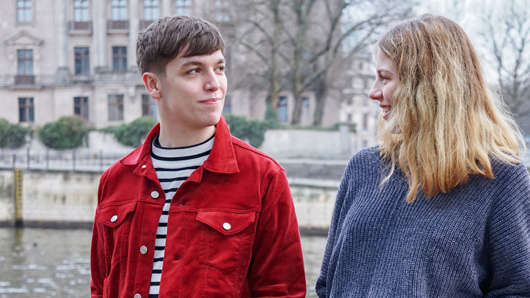 Ein junger Mann und eine junge Frau stehen in Berlin an der Spree. Sie schauen sich an.