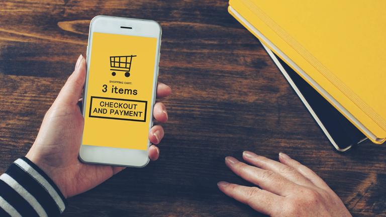 Symbolfoto: Eine Hand hält ein Smartphone auf der ein symbolischer Kaufakt getätigt wird