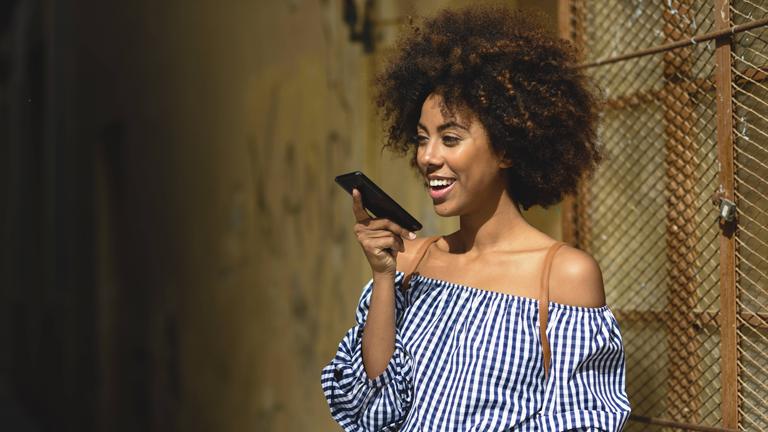 Eine junge Frau spricht in ihr Smartphone
