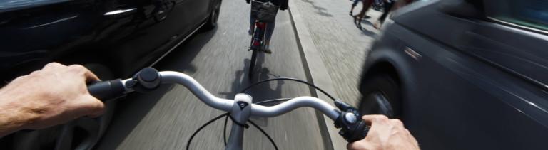Auf einer Straße in Berlin wird ein Fahrradfahrer links von einem Auto überholt. Mit wenig Abstand. Rechts steht ein parkendes Auto.