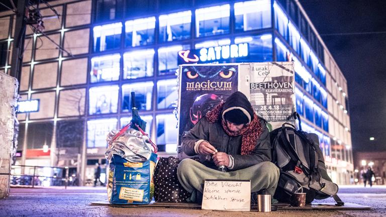 Ein Obdachloser sitzt am Alexanderplatz in Berlin