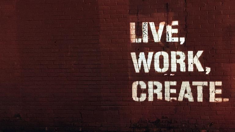 Auf eine roten Backsteinwand steht in weißen Blockbuchstaben: Live, Work, Create