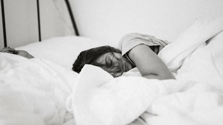 Ein Frau liegt im Bett und schläft, schwarz-weiß-Foto.