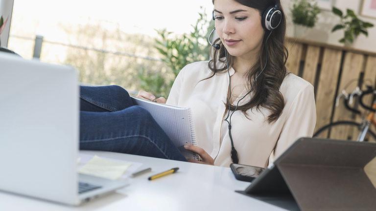 Eine Frau sitzt zu Hause am Schreibtisch, sie trägt ein Headset. Auf dem Schreibtisch stehen Laptop und Tablet. Sie macht sich Notizen auf einem Block.