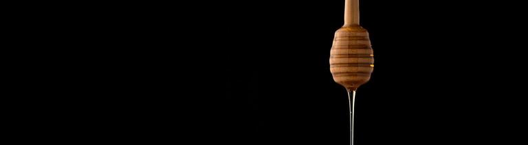 Honig läuft an einem Honiglöffel aus Holz herunter. Der Löffel hat an einem Ende eine runde Spirale.