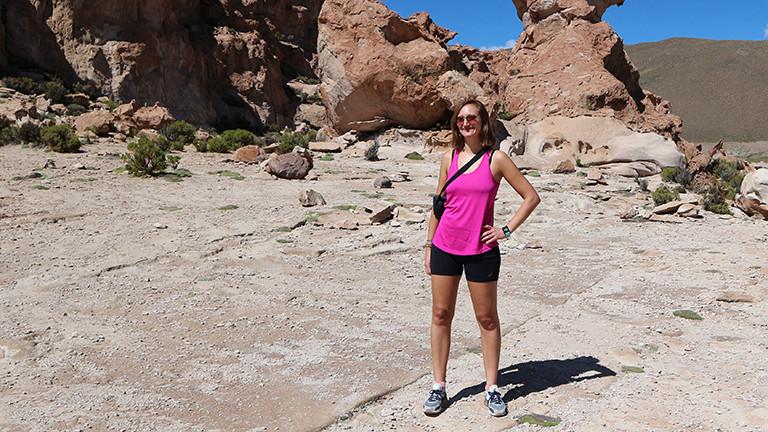 Victoria Reith im Urlaub; sie steht bei Sonnenschein vor einer Felsenformation.