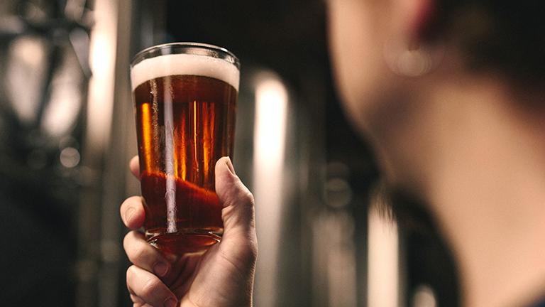 Eine Hand hält ein Glas Bier in die Luft