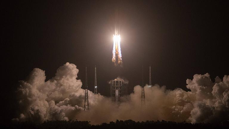 Eine Rakete startet, über dem Boden dicke Qualmwolken