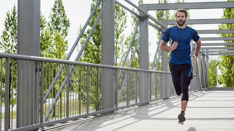 Ein Mann joggt über eine Brücke