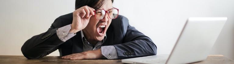 Ein Mann sitzt vorm Computer und ärgert sich.