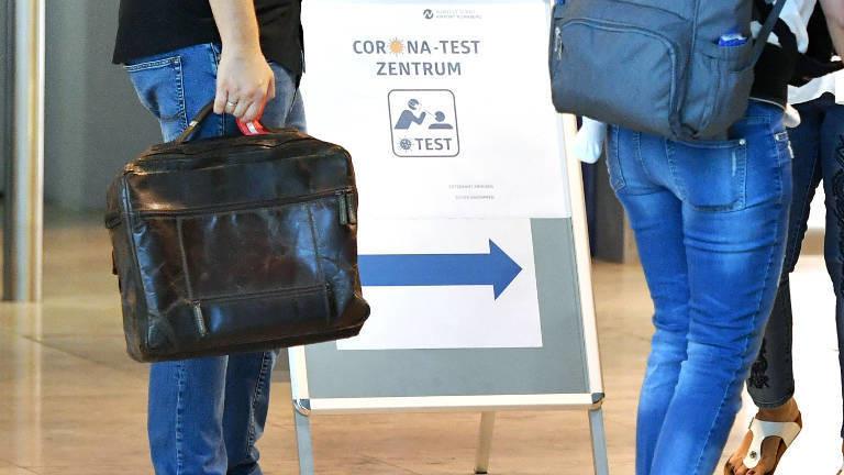 Ein Schild an einem Flughafen, das zum Coronatest-Zentrum führt.