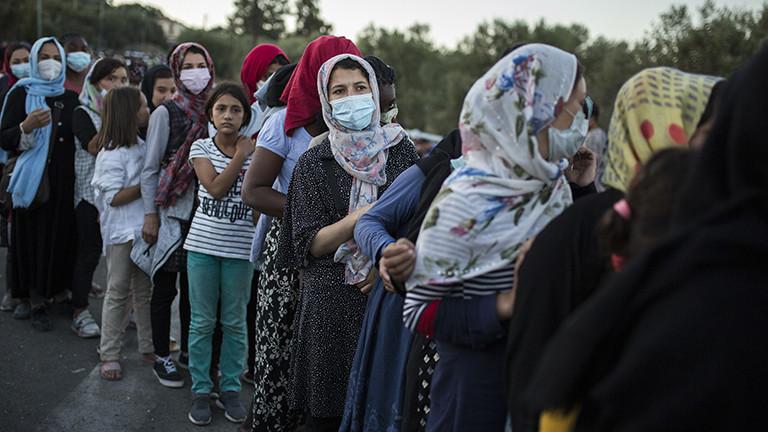 Viele Frauen und Mädchen stehen in einer langen Schlange für Essen an. Die Frauen tragen Mundschutz. Sie haben im Flüchtlingslager Moria gelebt, das durch einen Brand zerstört wurde (10.09.2020); Foto: dpa