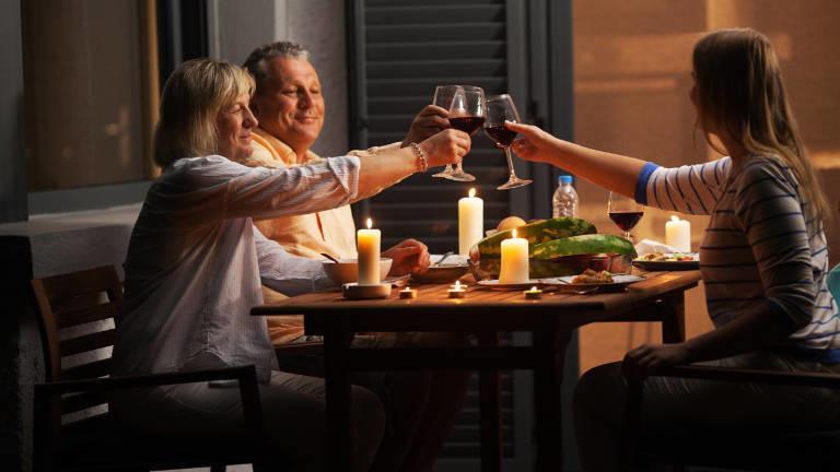 Drei Personen am Tisch mit einem Glas Wein in der Hand